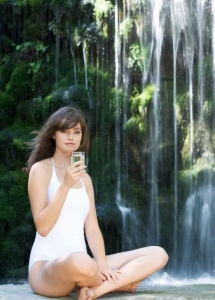 A woman drinkig a glass of water by a waterfall