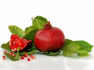 Ripe pomegranates on green leaves isolated on white background